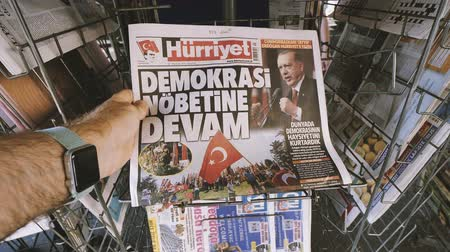 buy newspaper : PARIS, FRANCE - JUL 16, 2018: Man POV buying Turkish newspaper Hurriyat featuring Turkish newly elected president Recep Tayyip Erdogan