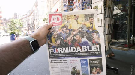 végső : PARIS, FRANCE - JUL 16, 2018: Man buying Dutch newspaper announcing France champion title after French national football team won their FIFA World Cup 2018 with Breaking Formidable title Stock mozgókép