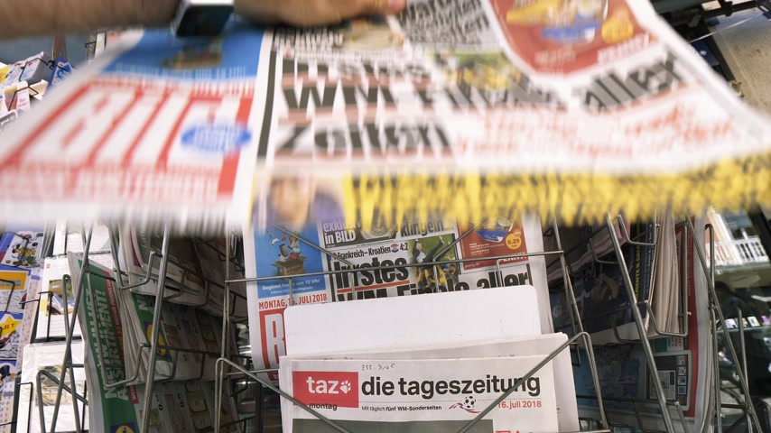 végső : PARIS, FRANCE - JUL 16, 2018: Man buying Die Bild German newspaper announcing France champion title after French national football team won their FIFA World Cup 2018 final game against Croatia in Moscow