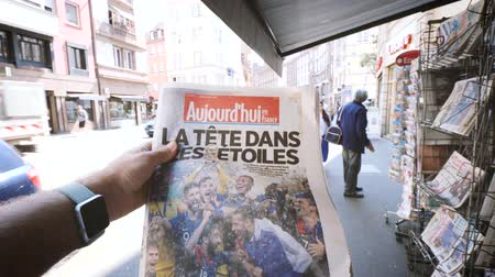 el : PARIS, FRANCE - JUL 16, 2018: Man POV buying newspaper announcing France champion title after French national football team won their FIFA World Cup 2018 final game against Croatia in Moscow Stock mozgókép