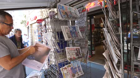 el : PARIS, FRANCE - JUL 16, 2018: Smoking man buying  newspaper announcing France champion title after French national football team won their FIFA World Cup 2018 final game against Croatia in Moscow