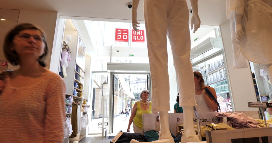 uniqlo : PARIS, FRANCE - JUN 30, 2018: People shopping inside Uniqlo fashion store entrance facade in France with French fashionista people woman admiring Japanese fashion and ready-to-wear