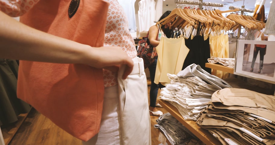 uniqlo : PARIS, FRANCE - JUN 30, 2018: Woman measuring Uniqlo pants in Uniqlo store - woman admiring Japanese fashion and ready-to-wear Stock Footage