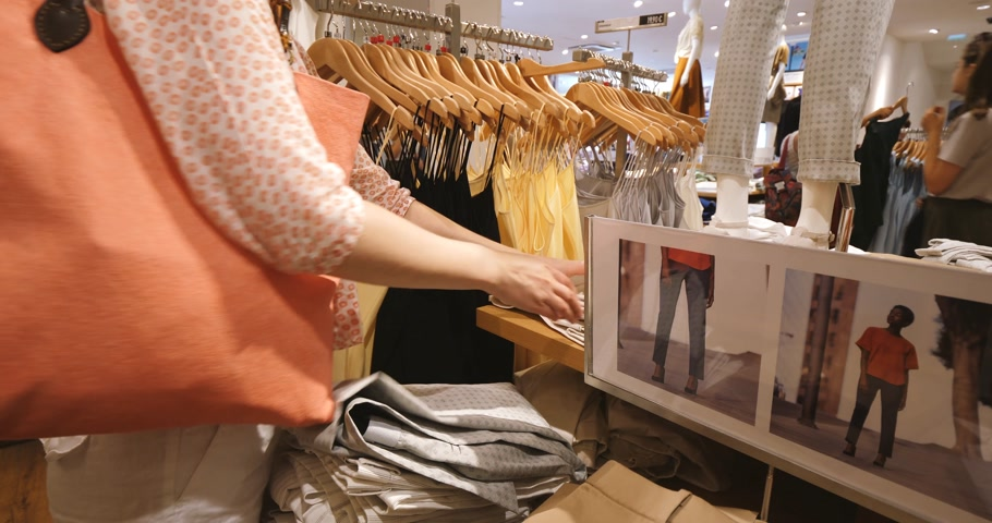 uniqlo : PARIS, FRANCE - JUN 30, 2018: Woman searching for her size Uniqlo pants in Uniqlo store - woman admiring Japanese fashion and ready-to-wear Stock Footage