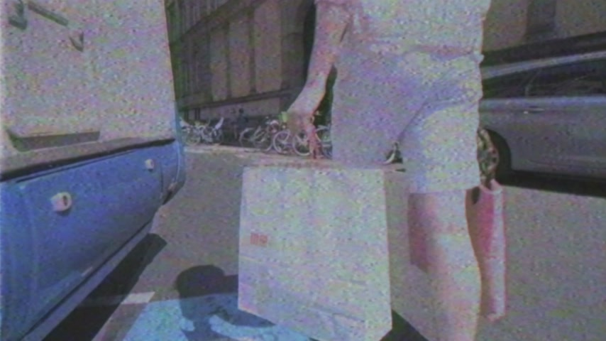 uniqlo : STRASBOURG, FRANCE - CIRCA 2018: French woman walking on the street in France with shopping bag from UNIQLO Japanese fashion store - vintage VHS tape film effect