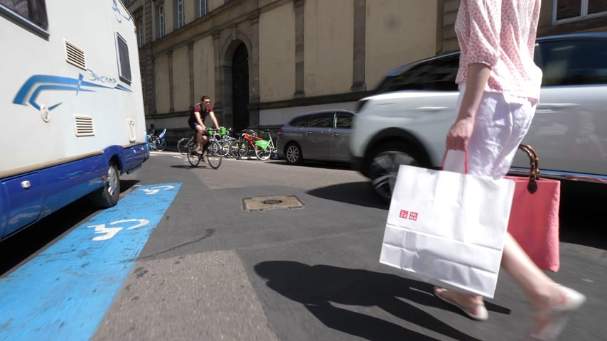 uniqlo : STRASBOURG, FRANCE - CIRCA 2018: Following rear view of French woman walking on the street in France with shopping bag from UNIQLO Japanese fashion store Stock Footage