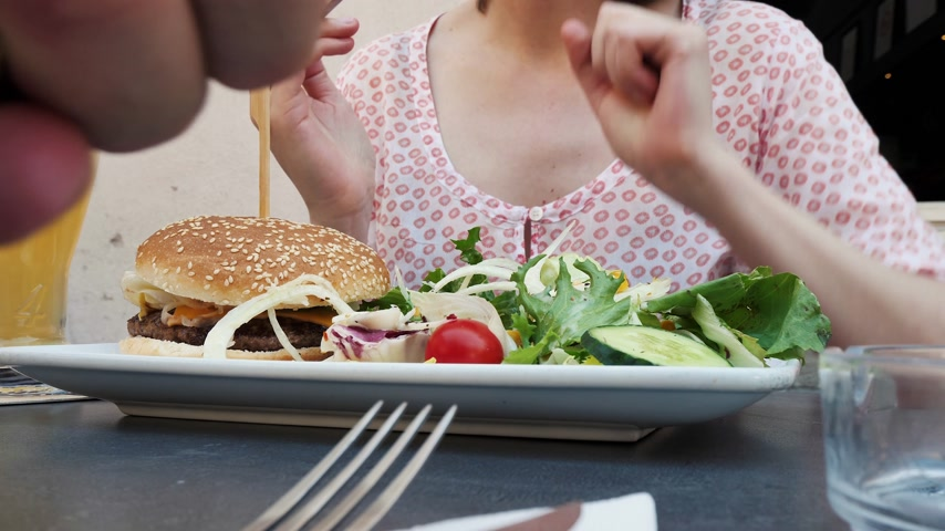 sajtburger : Woman and man eating tasteful hamburger burger with salad and fries on the outdoor terrace of a French city - drinking beer - using fork