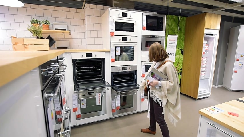 furnishing : PARIS, FRANCE - CIRCA 2018: Multiple contemporary IKEA furniture store with woman customer browsing through diverse furniture, decoration warehouse goods -