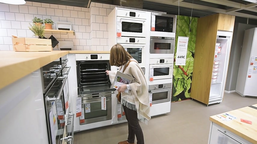 showcase : PARIS, FRANCE - CIRCA 2018: Multiple contemporary IKEA furniture store with woman customer browsing through diverse furniture, decoration warehouse goods oven stove selection in kitchen