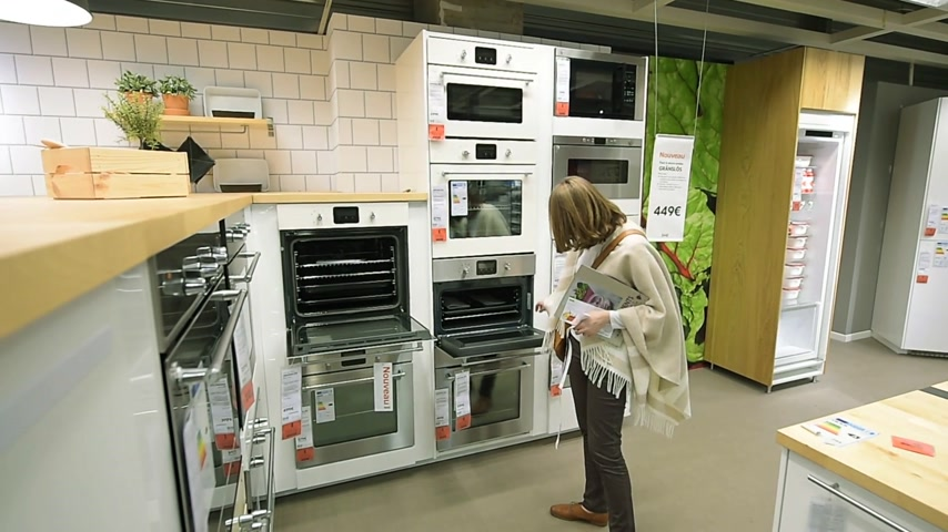 furnishing : PARIS, FRANCE - CIRCA 2018: Woman buying oven stove kitchen IKEA furniture browsing through diverse furniture, decoration warehouse goods