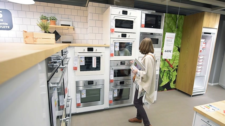 ikea : PARIS, FRANCE - CIRCA 2018: Multiple contemporary IKEA furniture store with woman customer browsing through diverse furniture, decoration warehouse goods selecting perfect oven stove