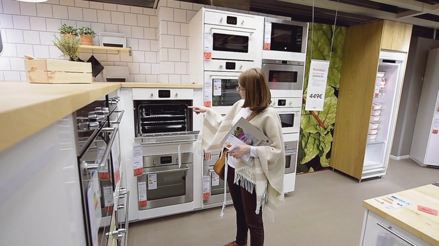 furnishing : PARIS, FRANCE - CIRCA 2018: Multiple contemporary IKEA furniture store with woman customer browsing through diverse furniture, decoration warehouse goods selecting perfect oven stove