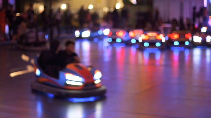 sıkı : Time-lapse fast motion of nighttime view of funny atmosphere at the amusement park with multiple bumper cars accidents happy people silhouettes  - real game Stok Video