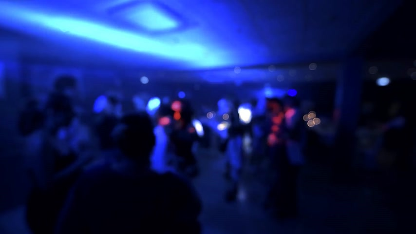 новобрачный : Defocused view of great wedding party with silhouettes of people dancing on the dancefloor with the disco lights glowing in the background multiple colors