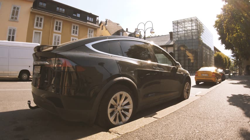 tilt down : CHAMBERY, FRANCE - CIRCA 2018: Tilt-down to Luxury Tesla Model X electric car SUV parked on French street on a sunny day Stock Footage