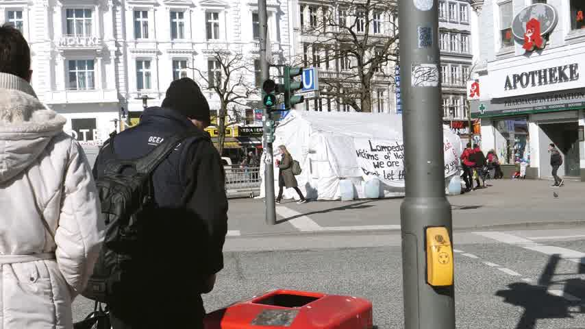migrants : HAMBURG, GERMANY - CIRCA 2018: POV at pedestrians crossing street in Hamburg center with migrants and pedestrians tent with inscriptions about war in Libya, NATO presence and Lampedusa