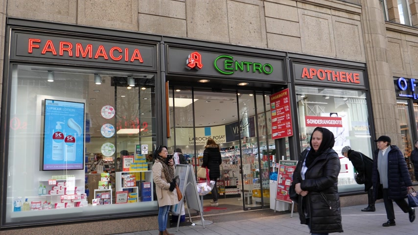 boticário : HAMBURG, GERMANY - CIRCA 2018: Farmacia Apotheke Centro central Hamburg shopping street drug-store with neons sign and pedestrians entering the old building Vídeos