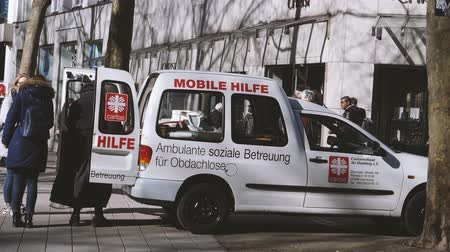 hamburg : HAMBURG, GERMANY - CIRCA 2018: Nun offering to person diverse help from the mini van Mobile Hilfe, mobile help by Caritas orgnization - the Catholic relief, development and social service organizations operating in over 200 countries and territories world