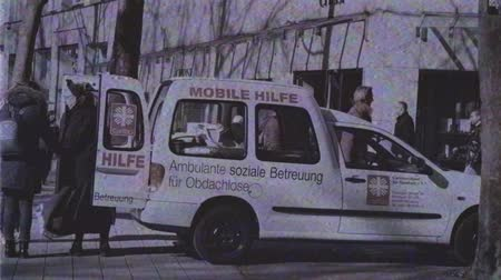 bem estar : HAMBURG, GERMANY - CIRCA 2018: Vintage VHS film effect nun offering to person diverse help from the mini van Mobile Hilfe, mobile help by Caritas orgnization - the Catholic relief, development and social service organizations operating in over 200 countri