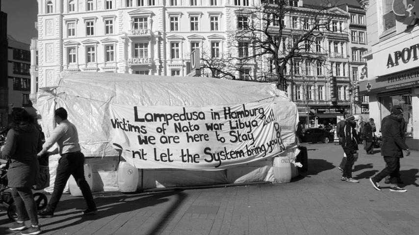 göçmen : HAMBURG, GERMANY - CIRCA 2018: Black and white slow motion scene with pedestrians walking in front of migrants tent with inscriptions about war in Libya, NATO presence and Lampedusa island