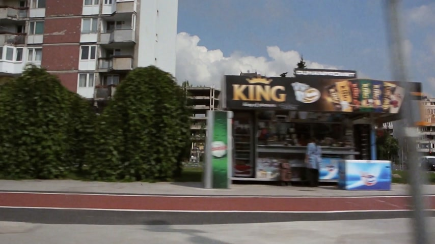 sosyalizm : Sarajevo, Bosnia and Herzegovina - Circa 2018: View on typical Yugoslav residential buildings and shops as seen from inside a vehicle driving on the streets of Sarajevo cinematic vintage tape