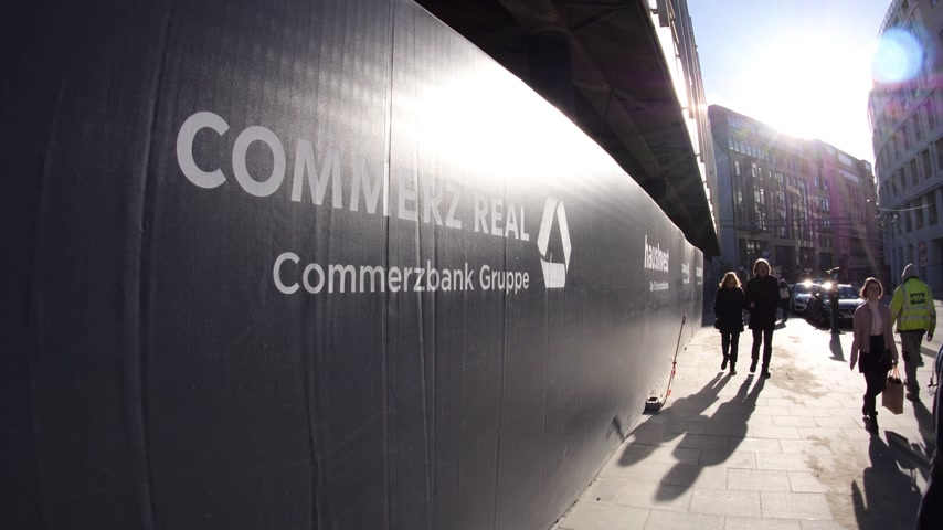 hamburg : HAMBURG, GERMANY - CIRCA 2018: People walking near construction site with sign logotype House Invest Commerzbank German Bank Commerz Real Stock Footage