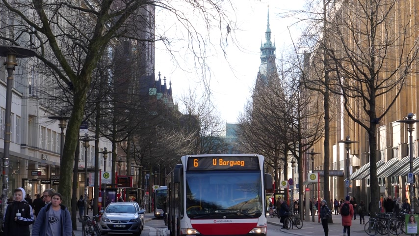 hamburg : HAMBURG, GERMANY - CIRCA 2018: Scania Hochbahn bus in central Hamburg with Majestic city-hall Rathaus Hamburg in the background - people walking commuting day spring public transportation Stock Footage
