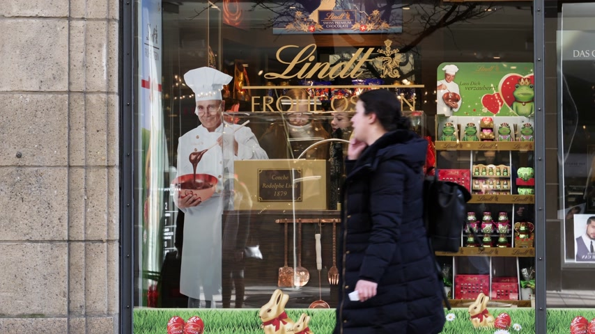 az yağlı : HAMBURG, GERMANY - CIRCA 2018: Lindt & Sprungli chocolate sweets store in central Hamburg on the Spitalerstrasse with people customers entering the sweets food store with Rodolphe Lindt portrait Stok Video