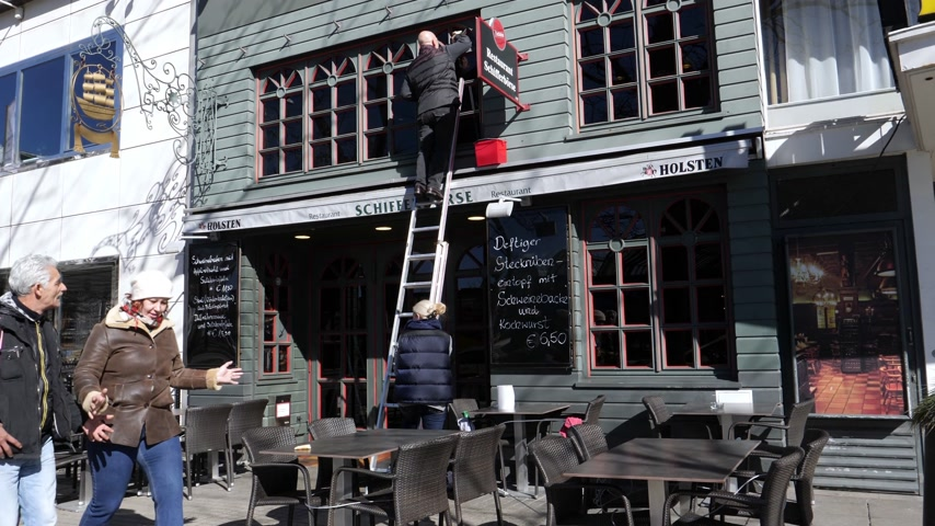hamburg : HAMBURG, GERMANY - CIRCA 2018: Owner on the ladder cleaning the windows of his restaurant Schifferborse Hamburg on Kirchenallee being helped by a woman