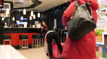 hamburg : HAMBURG, GERMANY - CIRCA 2018: Foodora food app delivery employee loading hot food in the pink temperature controlled backpack inside German restaurant Stock Footage