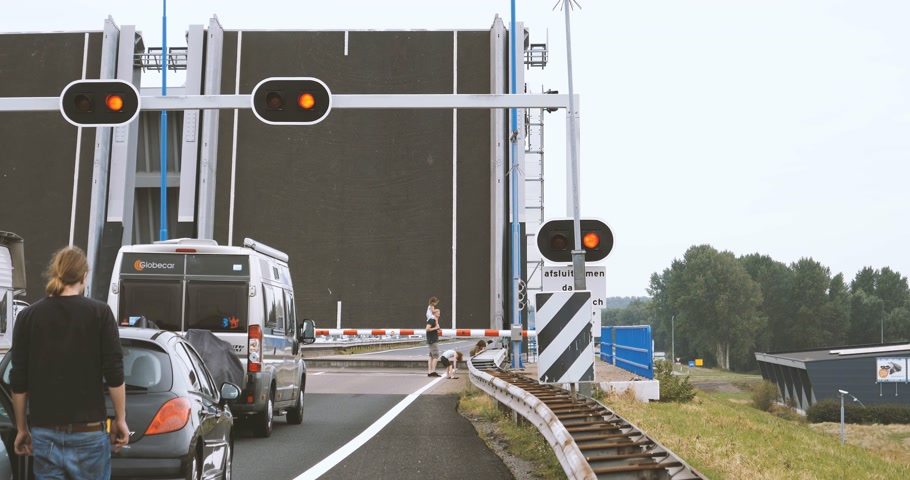 drawbridge : NETHERLANDS - CIRCA 2018: Bridge raised for river traffic as seen from the Dutch highway and father with three kids admiring the passing boats drawbridge Stock Footage