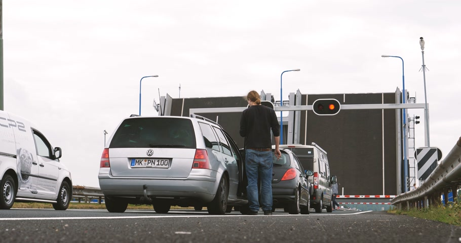 volkswagen : NETHERLANDS - CIRCA 2018: Low angle view of man waiting admiring next to his Volkswagen car the drawbridge bridge raised for river traffic as seen from the Dutch highway Stock Footage