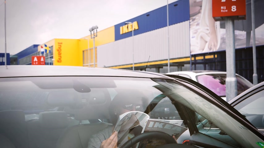 ikea : DELFT, NETHERLANDS - CIRCA 2018: Cinematic view from street woman reading IKEA catalog inside car parked in front of the main store in Netherlands, headquarter of IKEA Global slow motion Stock Footage