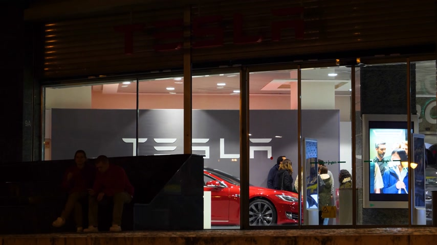 corte : Lisbon, Portugal - Circa 2018: Tesla Showroom inside large Shopping mall in Lisbon featuring a red sport tesla limousine and a couple deciding to buy the first electric car