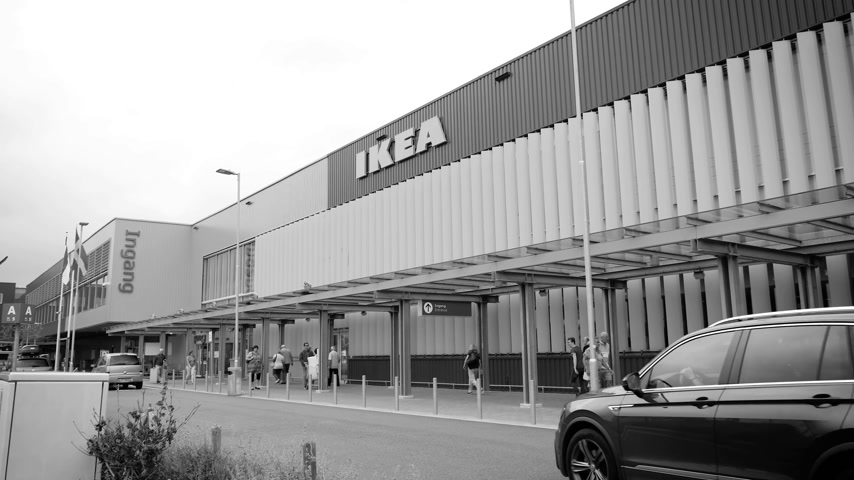 ikea : DELFT, NETHERLANDS - CIRCA 2018: Ikea furniture store with customers walking to the entrance near the large facade - black and white Stock Footage