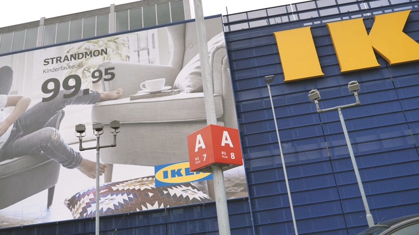 ikea : DELFT, NETHERLANDS - CIRCA 2018: Pan to the large facade building of IKEA furniture store with big yellow logotype and advertising board featuring furniture - headquarter in Delft