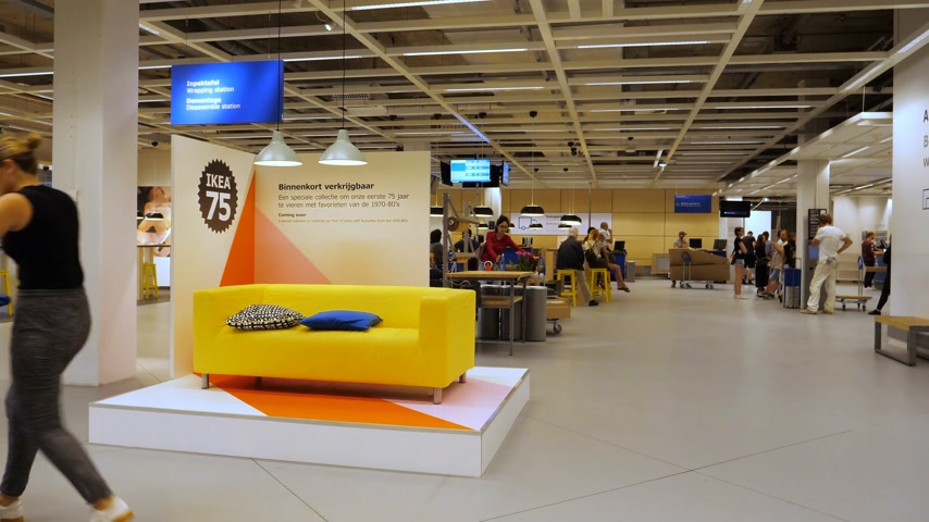 retailer : DELFT, NETHERLANDS - CIRCA 2018: Service client area with hero object yellow sofa and Ikea 75 years logotype anniversary
