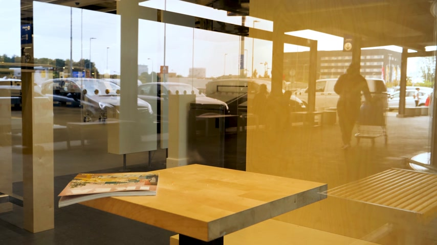 katalog : DELFT, NETHERLANDS - AUG 23, 2018: Ikea furniture catalogue magazine on the table made by IKEA - view from the street through glass inside store