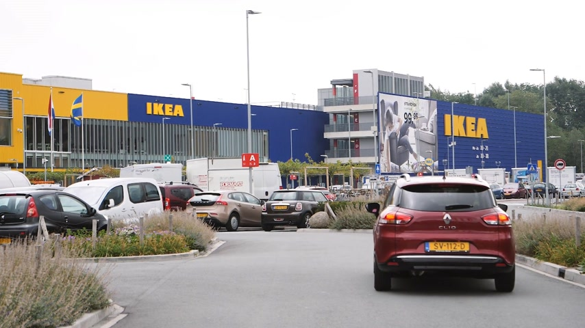 miscellaneous : DELFT, NETHERLANDS - CIRCA 2018: Slow motion cinematic news footage of Renault car heading toward IKEA furniture warehouse store parking