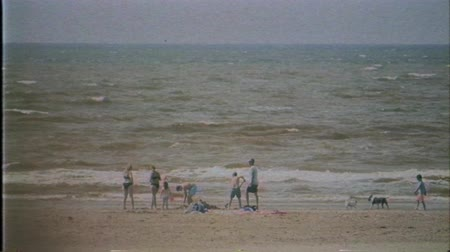 holandês : IJmuiden, Netherlands - Circa 2018: Sunny beach with people family sunbathing on the Dutch coast beach seaside - vintage VHS film effect