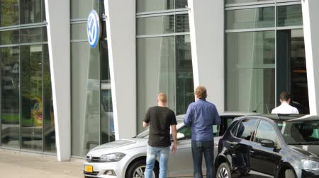 podání ruky : HAARLEM, NETHERLANDS - CIRCA 2018: Young businessman presenting the new Volkswagen Golf electric hybrid car to customer, trade-in or new car purchase or servicing the automobile in Volkswagen showroom dealership