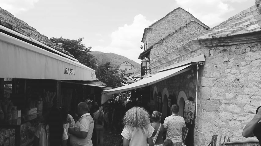 restaurante : MOSTAR, BOSNIA AND HERZEGOVINA - CIRCA 2018: View from Mostar Stari most bridge of tourists walking up and down busy bazar street in the Mostar old city on a hot summer day - black and white