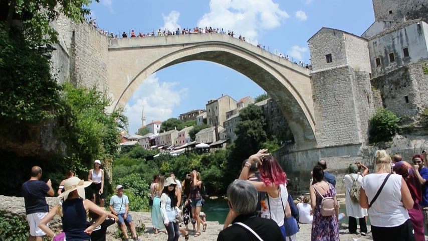 yugoslavia : MOSTAR, BOSNIA AND HERZEGOVINA - CIRCA 2018: View of tourist crowd admiring and taking photos of UNESCO heritage Mostar Stari most bridge while other tourists are crossing it on a hot summer day - low angel view