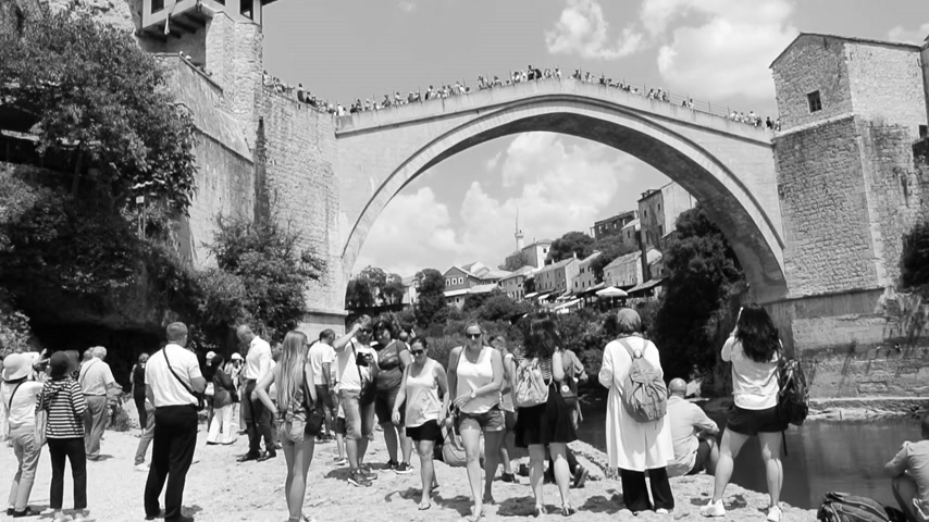 yugoslavia : MOSTAR, BOSNIA AND HERZEGOVINA - CIRCA 2018: People sightseeing UNESCO heritage Mostar Stari most bridge while other tourists are crossing it on a hot summer day black and white Stock Footage