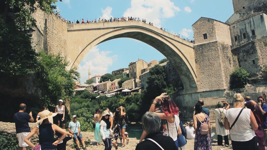 yugoslavia : MOSTAR, BOSNIA AND HERZEGOVINA - CIRCA 2018: View of tourist crowd admiring and taking photos of UNESCO heritage Mostar Stari most bridge while other tourists are crossing it on a hot summer day cinematic, Stock Footage