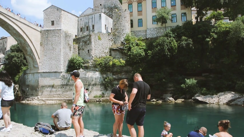 balkan : MOSTAR, BOSNIA AND HERZEGOVINA - CIRCA 2018: Hundreds of tourists admiring and taking photos of UNESCO heritage Mostar Stari most bridge with horizontal panning on turquoise Neretva river on a hot summer day