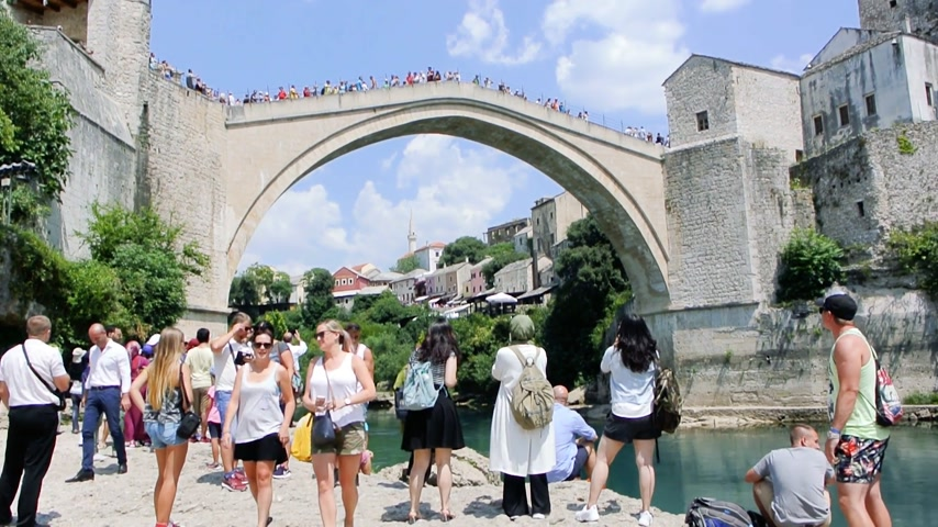 yugoslavia : MOSTAR, BOSNIA AND HERZEGOVINA - CIRCA 2018: Pan over large crowd of people admiring and taking photos of UNESCO heritage Mostar Stari most bridge with horizontal panning on Neretva river on a hot summer day Stock Footage