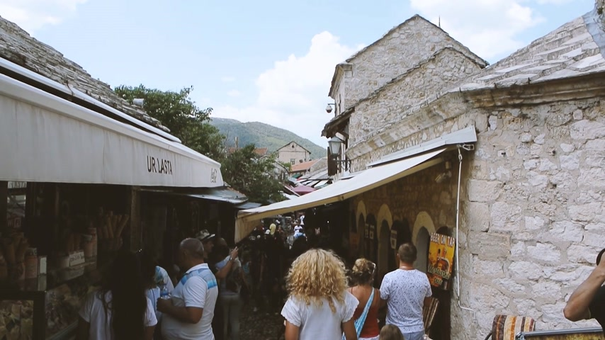 балканский : MOSTAR, BOSNIA AND HERZEGOVINA - CIRCA 2018: View from Mostar Stari most bridge of tourists walking up and down busy bazar street in the Mostar old city on a hot summer day Стоковые видеозаписи