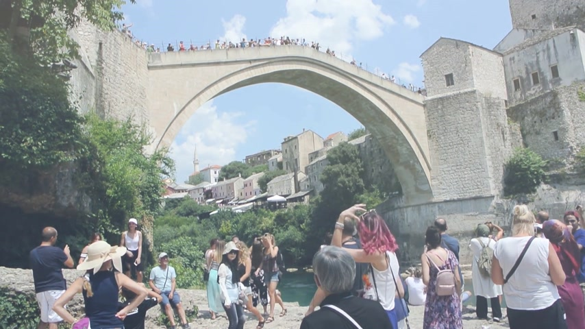 балканский : MOSTAR, BOSNIA AND HERZEGOVINA - CIRCA 2018: Large crowd of tourists admiring and taking photos of UNESCO heritage Mostar Stari most bridge while other tourists are crossing it on a hot summer day Стоковые видеозаписи