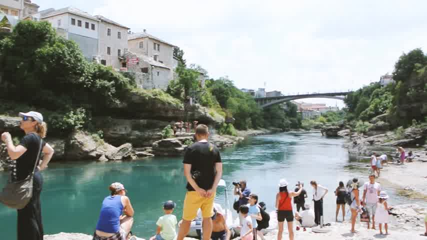 yugoslavia : MOSTAR, BOSNIA AND HERZEGOVINA - CIRCA 2018: Hundreds of tourists admiring and taking photos of UNESCO heritage Mostar Stari most bridge with horizontal panning on turquoise Neretva river on a hot summer day